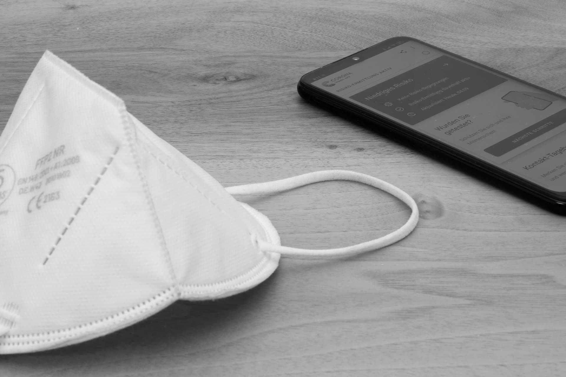 FFP2 Maske und daneben ein Smartphone mit der Corona Warn App